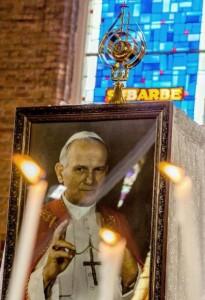 Une relique de Jean-Paul II est installée sur un portait de l'ancien pape durant une cérémonie en l'église Notre-Dame des Mineurs à Waziers, le 4 mai 2014 | Photo : AFP - Philippe Huguen