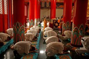 Les participants en prosternation avant une séance de méditation dans l'enceinte du temple principal de Dabao | Photo Karl-Stephan Bouthillette