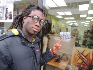 Marcellin Gbazaï, propriétaire de l'épicerie Mon Afrique au Saguenay, pointe un autocollant de la Fédération des Québécois de souche dans la vitrine de son commerce | Photo : via le Journal de Québec