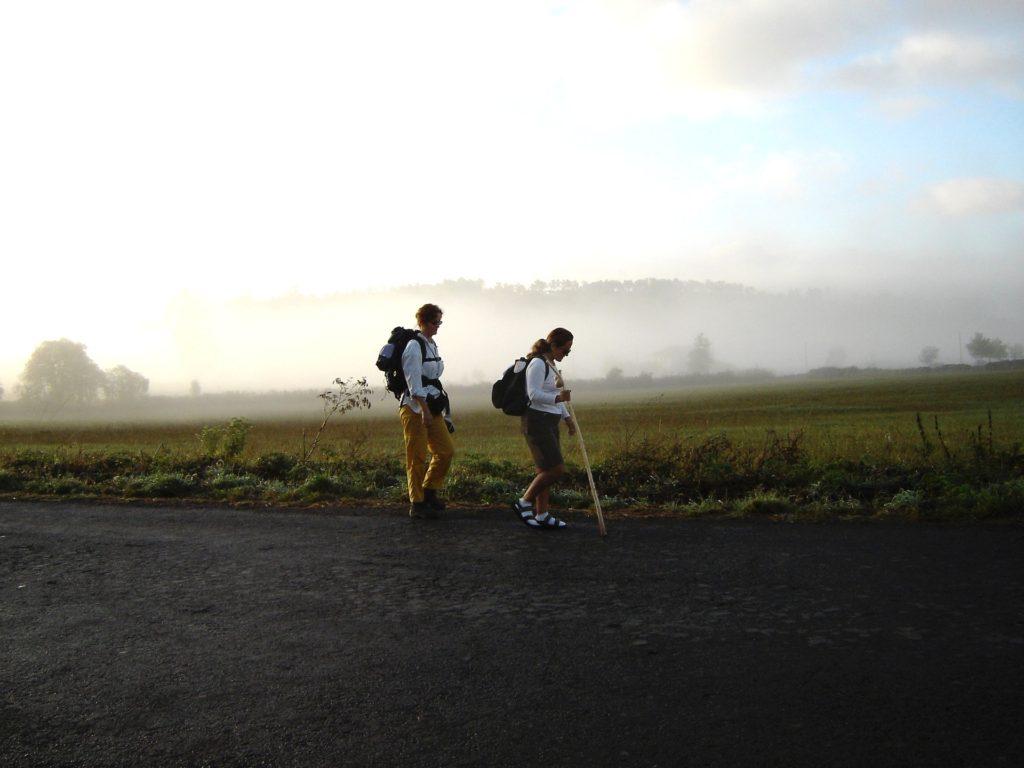 Deux pèlerins près d'un champ. Du brouillard au loin.